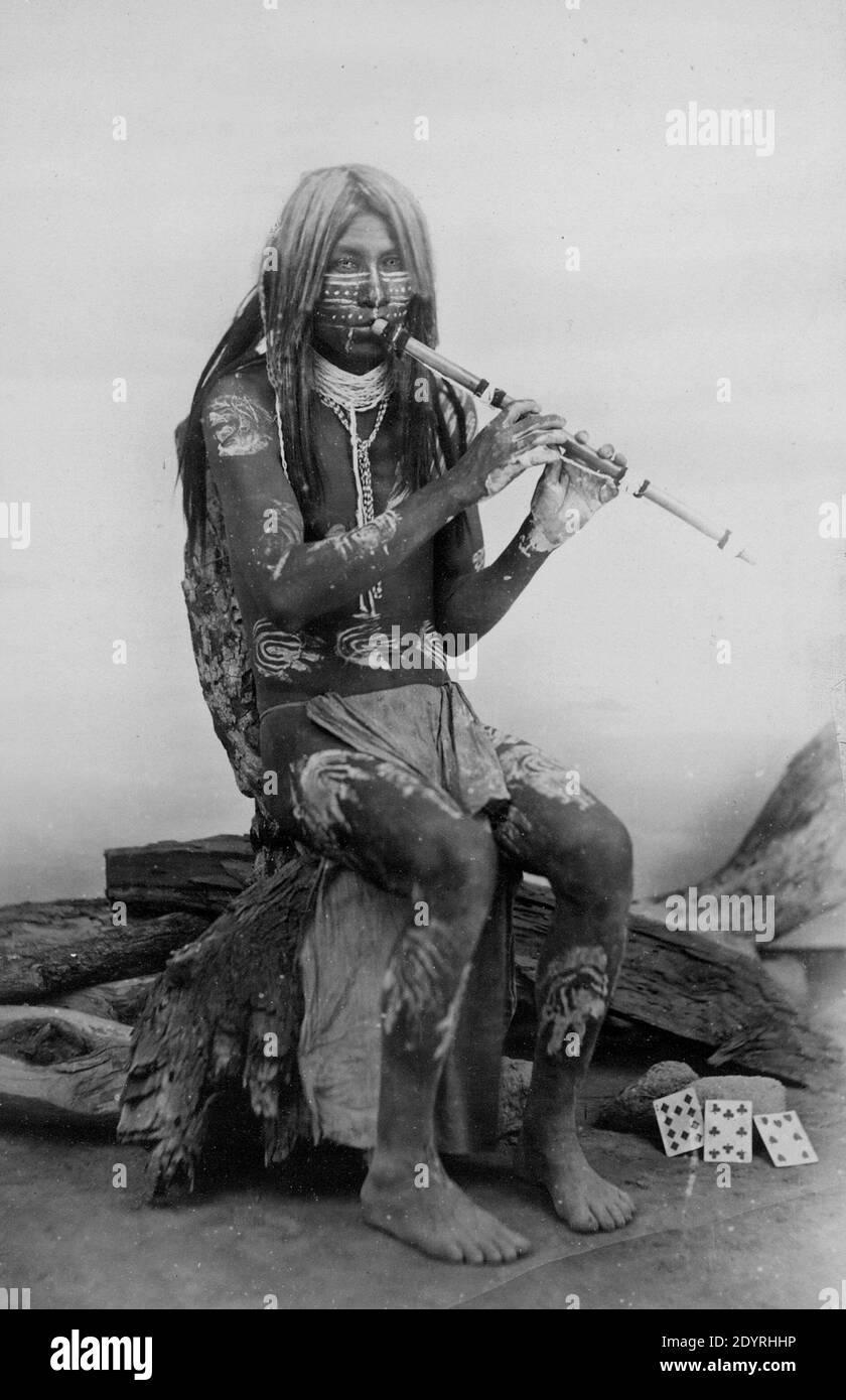 Musicien Yuma, Arizona. Yuma homme dans la peinture de corps, assis, face à l'avant, jouant une flûte. Banque D'Images