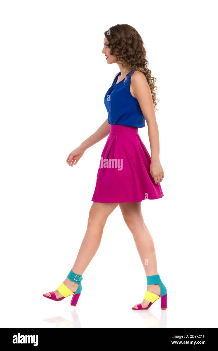 Vue latérale de la jeune femme marchant dans des talons hauts colorés, mini jupe rose et haut bleu. Prise de vue en studio sur toute la longueur isolée sur blanc. Banque D'Images