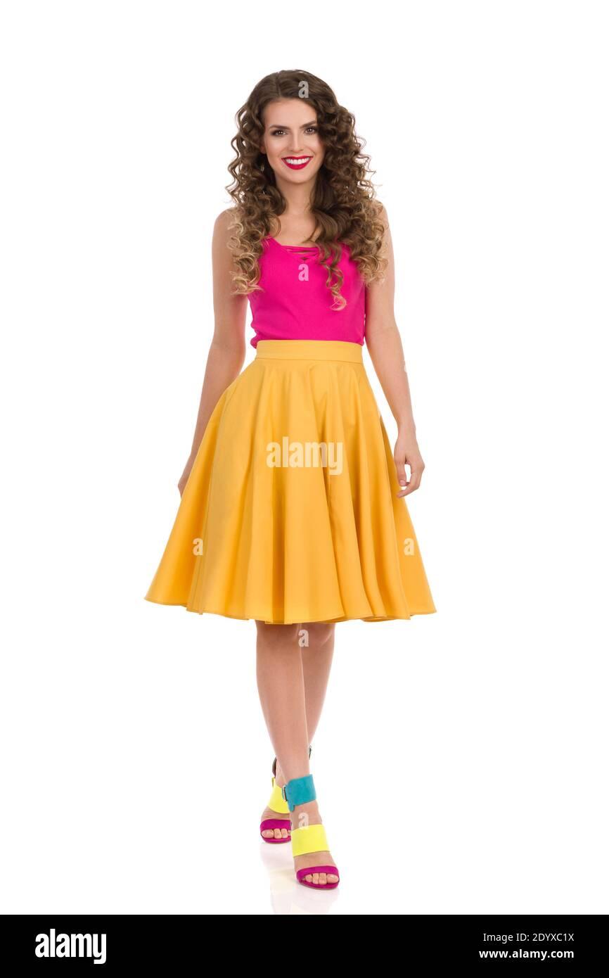 Vue de devant de la marche belle jeune femme dans des vêtements vibrants et hauts talons colorés. Prise de vue en studio sur toute la longueur isolée sur blanc. Banque D'Images