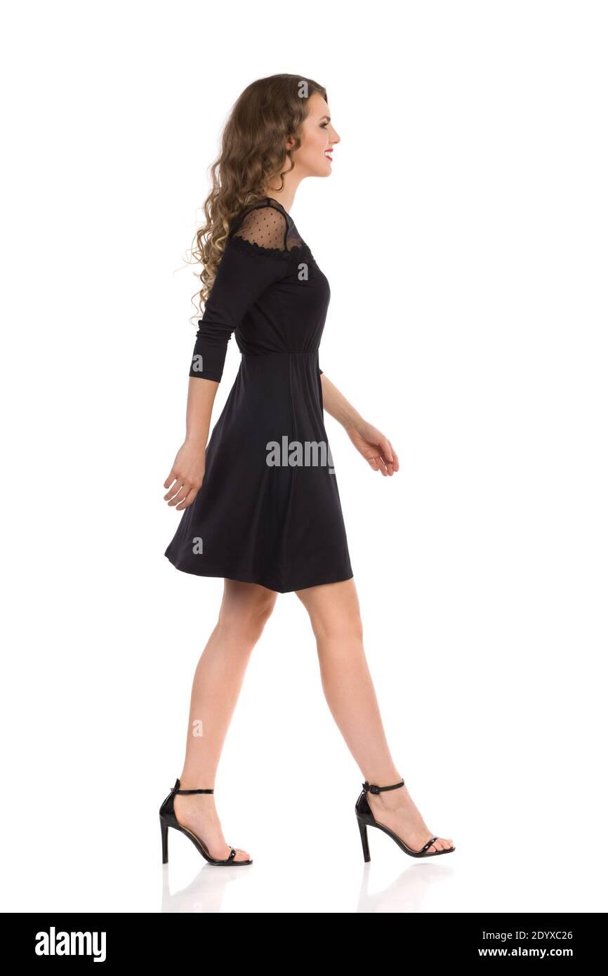 Vue latérale de la jeune femme marchant dans la robe élégante noire et les talons hauts. Prise de vue en studio sur toute la longueur isolée sur blanc. Banque D'Images