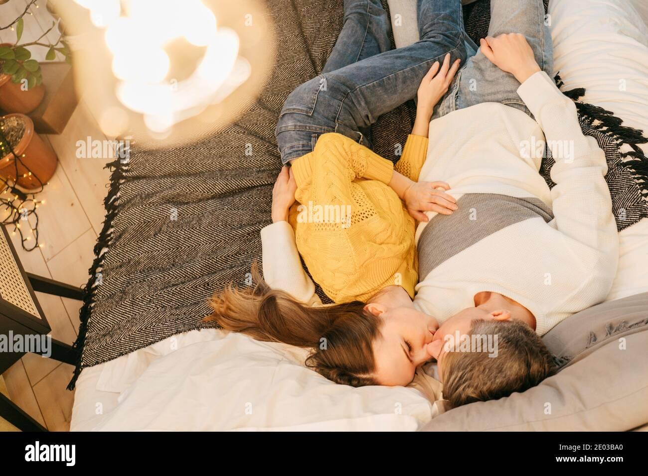 Histoire d'amour. Dans l'amour couple baiser sur le lit dans la soirée. Vue de dessus, ampoule au premier plan. Jaune et gris 2021. Banque D'Images