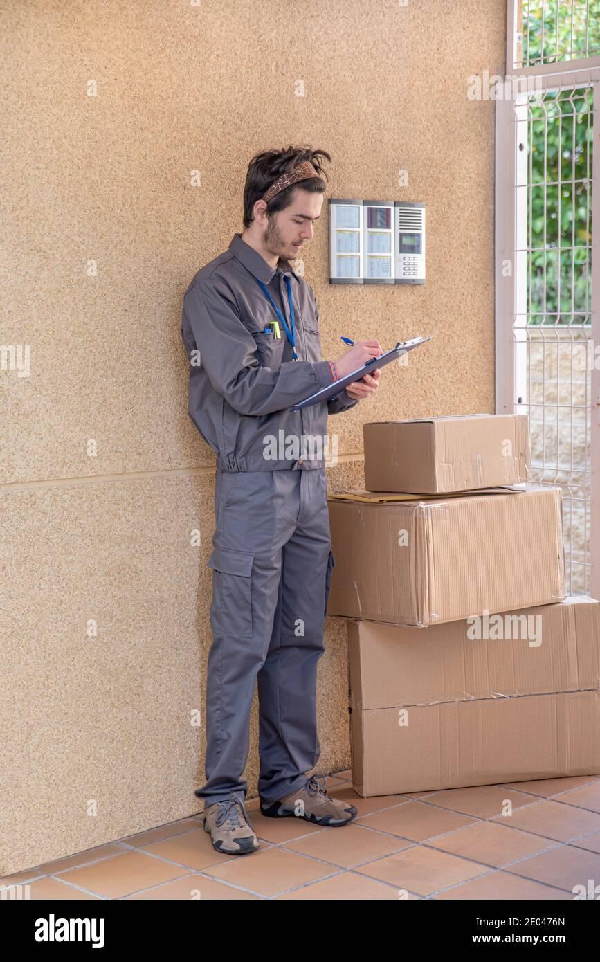 Messenger avec masque livre des paquets à la porte à côté de le portier Banque D'Images