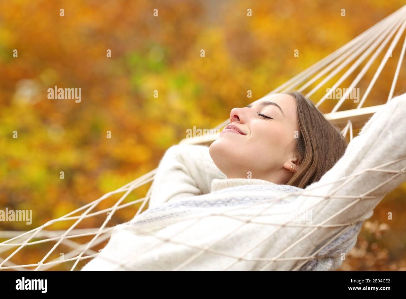 Femme détendue reposant sur un hamac en automne dans une forêt Banque D'Images