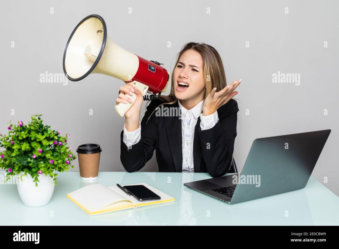 Angry businesswoman yelling avec haut-parleur de bureau Banque D'Images