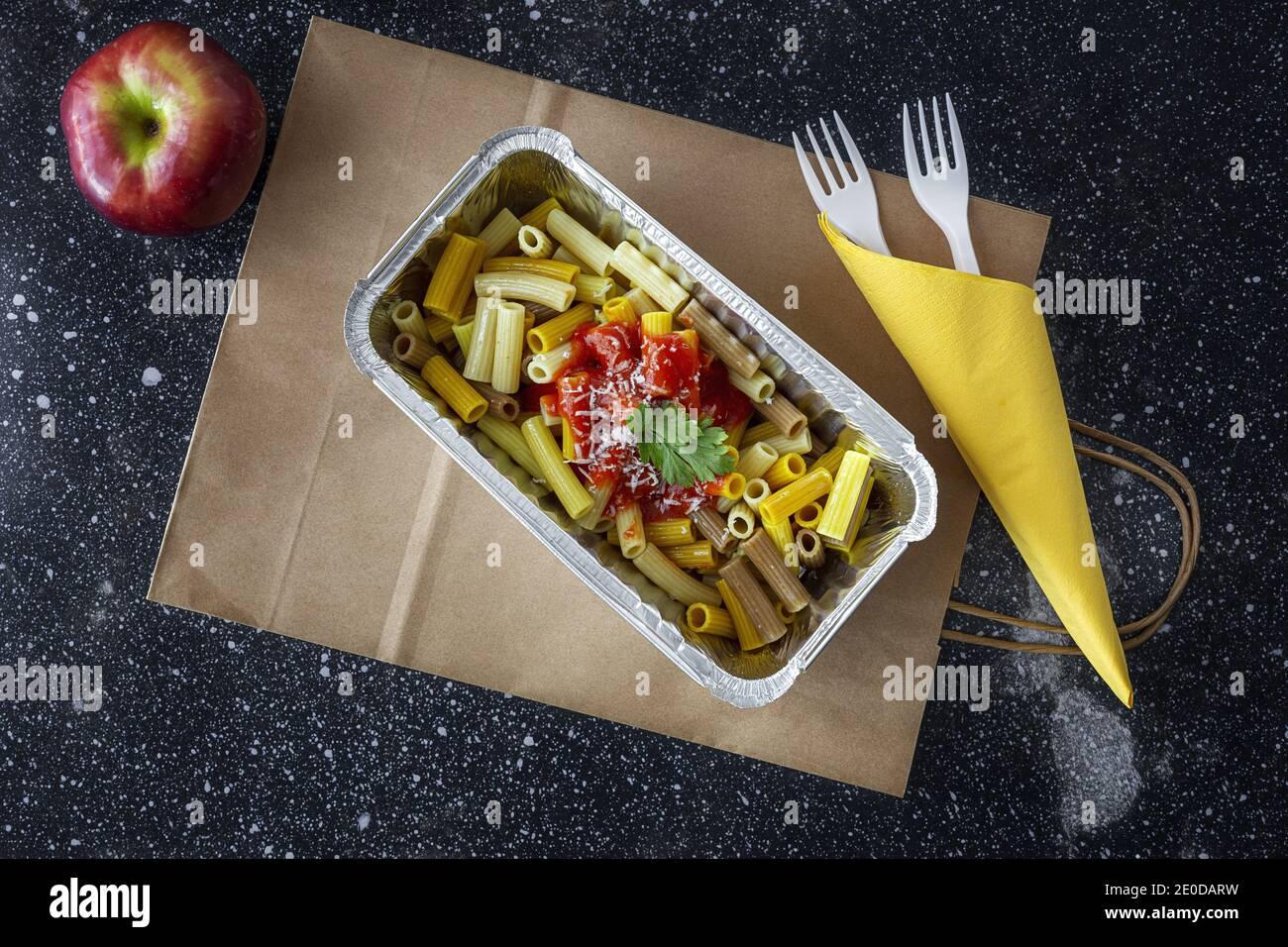 Du dessus de délicieux macaroni au ketchup et au fromage dans un récipient pour les plats à emporter sur la table avec la pomme Banque D'Images