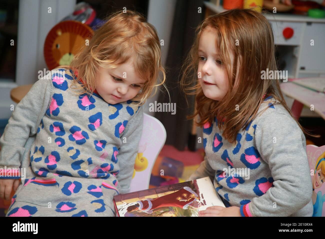 Une fille de 4 ans lisant un livre à sa petite sœur. Banque D'Images