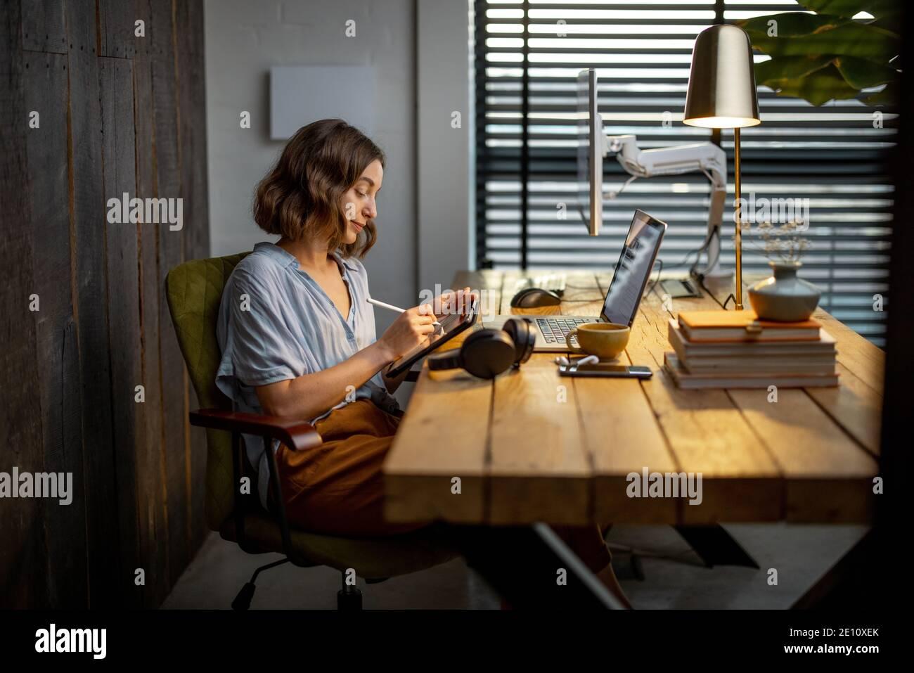 Jeune femme vêtue à la manière décontractée ayant un peu de travail créatif, dessin sur une tablette numérique, assis dans le bureau à la maison confortable et élégant Banque D'Images