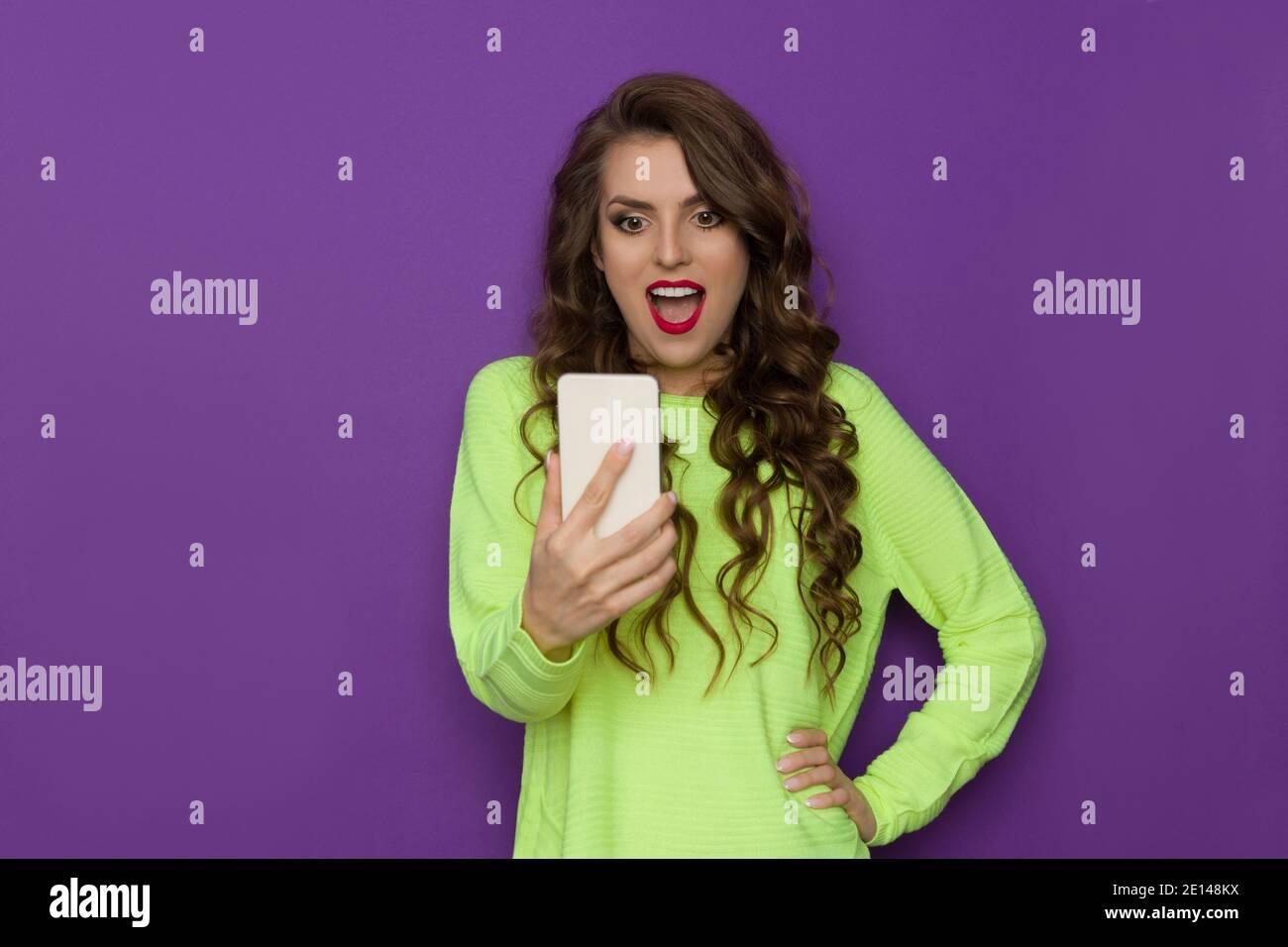 Une jeune femme choquée dans un chandail vert néon tient le téléphone, le regarde et crie. Vue avant. Taille haute, prise en studio sur fond violet. Banque D'Images