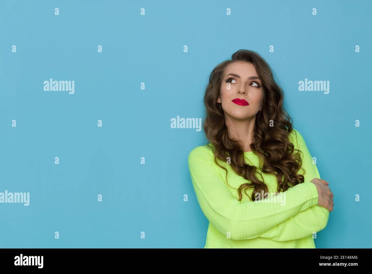 La jeune femme pensive en vert citron vert fluo tient les bras croisés, regardant vers le haut et pensant. Taille haute studio tourné sur fond bleu. Banque D'Images
