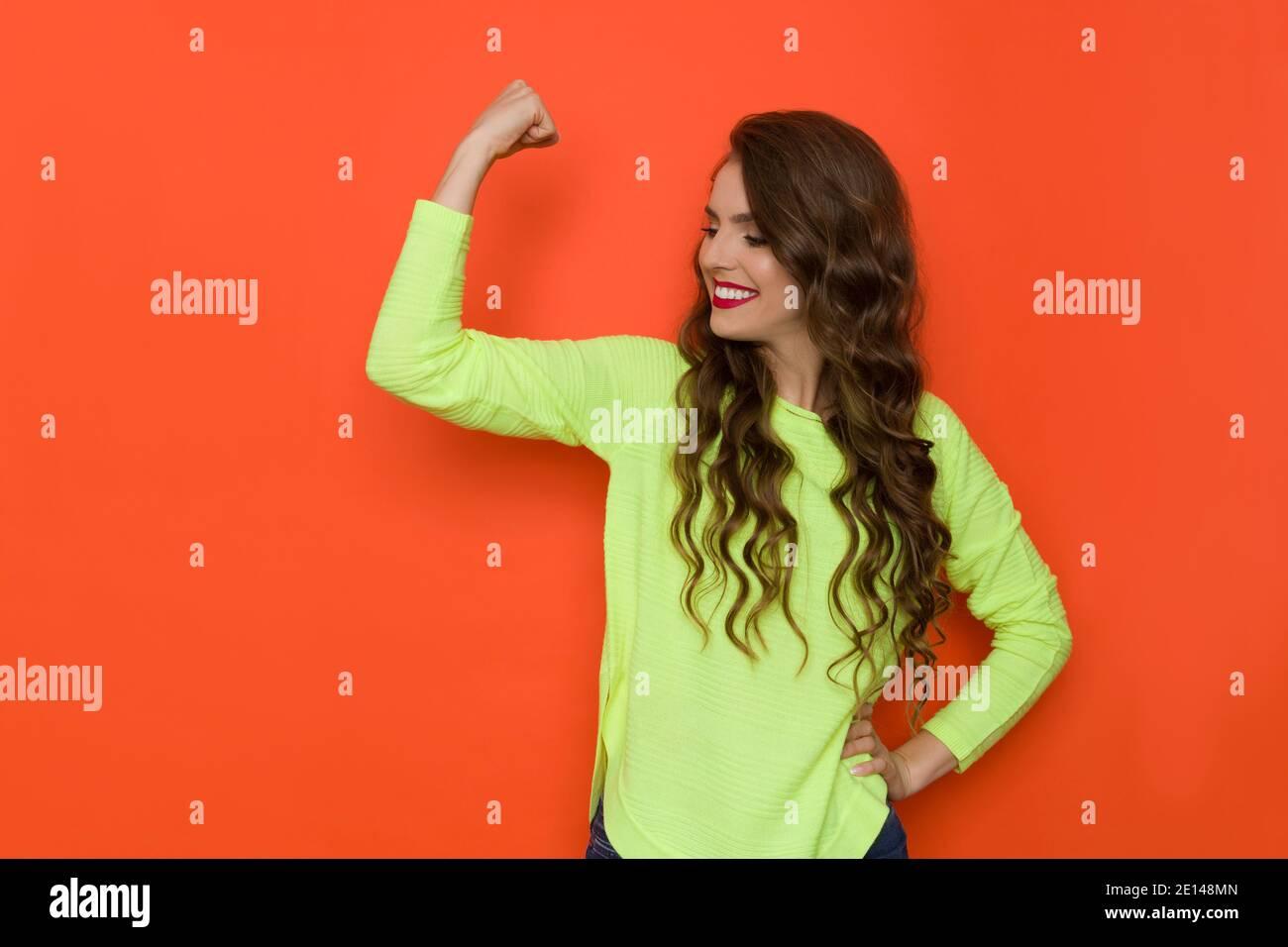 Une jeune femme heureuse en vert citron vert fluo tient le bras relevé, fléchissant le muscle, regardant loin et souriant. Taille haute studio tourné sur fond orange Banque D'Images