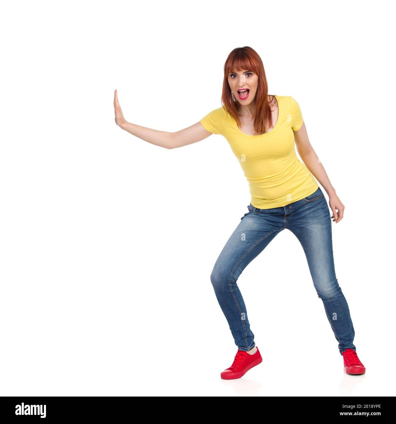 Une jeune femme excitée en chemise jaune, jeans et baskets rouges pousse quelque chose d'une main et crie. Vue avant. Prise de vue en studio pleine longueur isola Banque D'Images