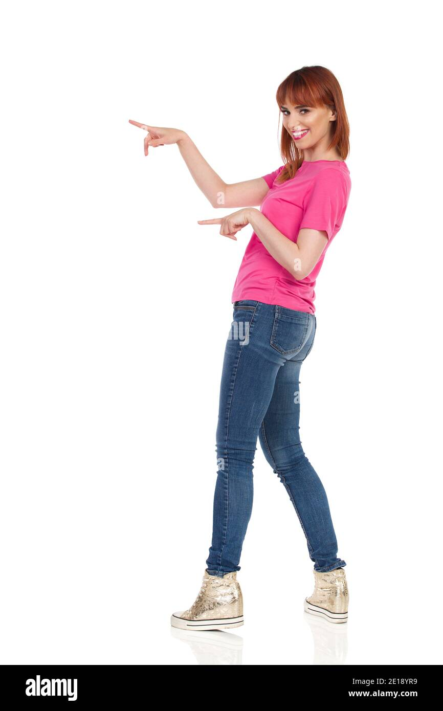 Jeune femme décontractée est debout, pointant sur le côté et souriant. Vue latérale. Prise de vue en studio sur toute la longueur isolée sur blanc. Banque D'Images