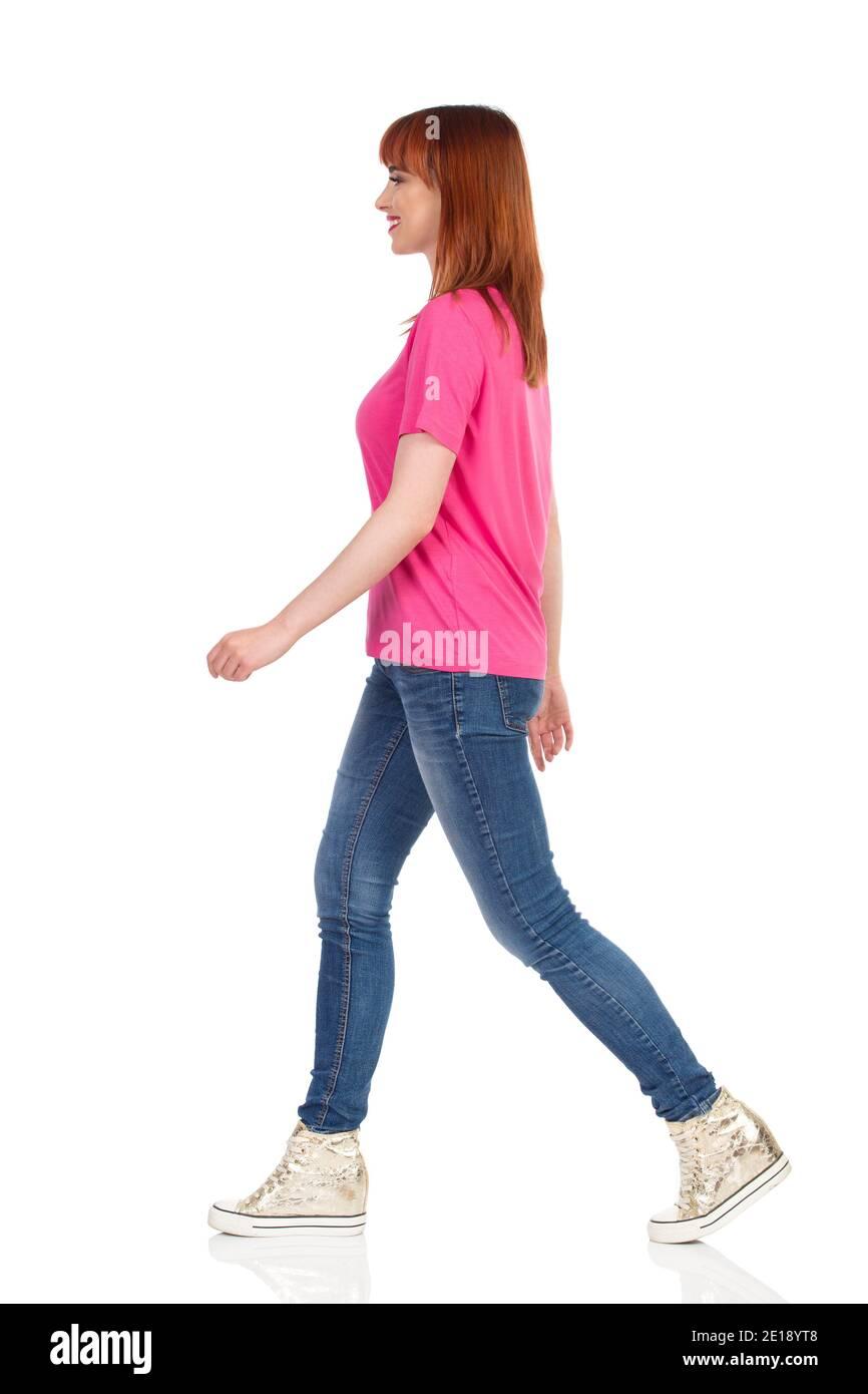 Une jeune femme heureuse et décontractée marche, regarde loin et sourit. Vue latérale. Prise de vue en studio sur toute la longueur isolée sur blanc. Banque D'Images