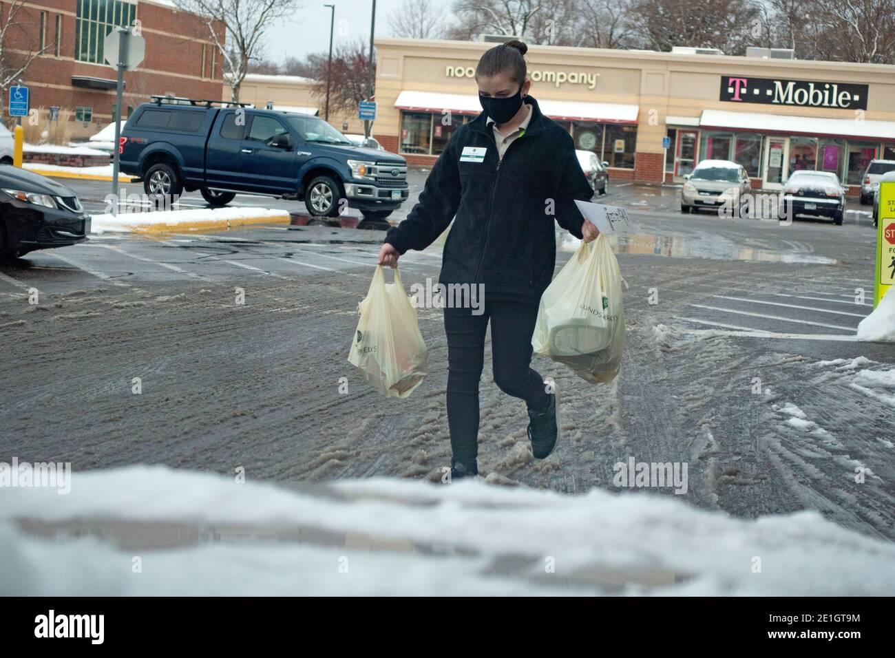 Un travailleur masqué apporte des produits d'épicerie au bord du trottoir à une voiture du Lunds Byerlys Grocery Store pendant la pandémie de Covid. St Paul Minnesota MN États-Unis Banque D'Images