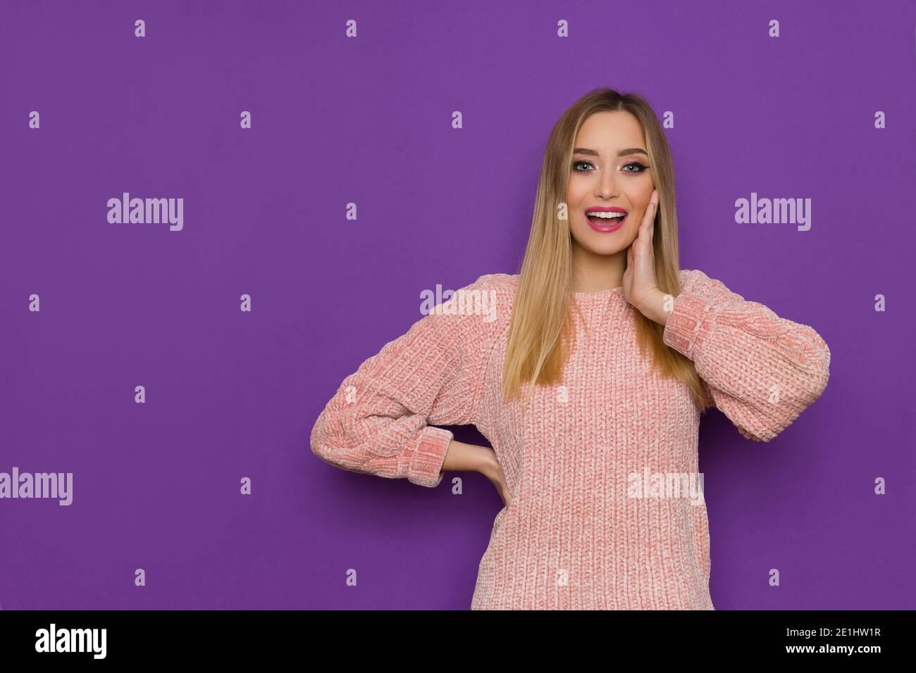 Une jeune femme surprise en chandail rose tient la main sur la joue, regarde la caméra et parle. Vue avant. Taille haute, prise en studio sur fond violet. Banque D'Images