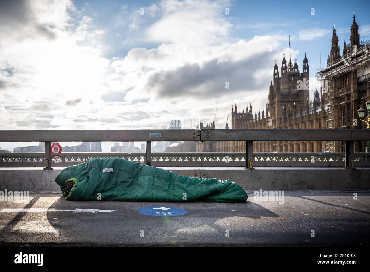 Un sommeil agace dans son sac de couchage à midi sur Westminster Bridge, Londres, Royaume-Uni. Banque D'Images