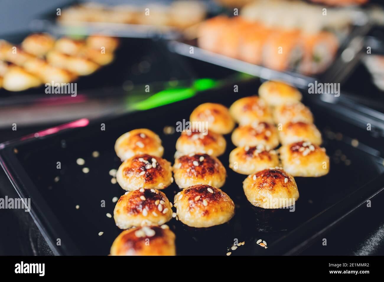 Table de cuisine asiatique avec divers types de plats chinois, nouilles, poulet, petits pains, sushis. Servi sur une ancienne table en bois, soupe asiatique, nouilles et sushi Banque D'Images