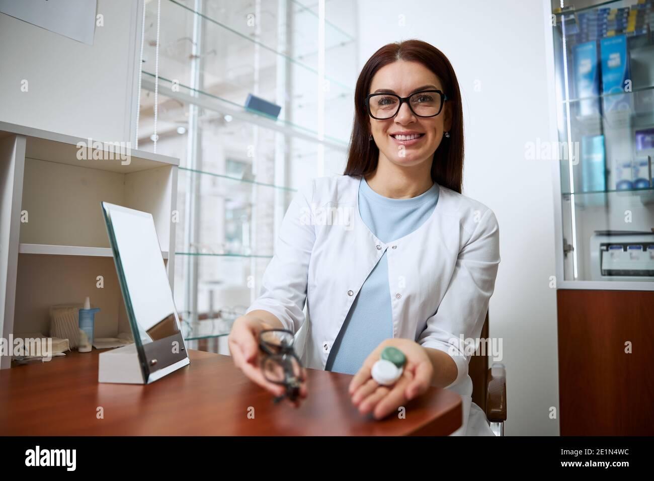 Ophtalmologiste compétent démontrant un ensemble de contacts et de lunettes Banque D'Images