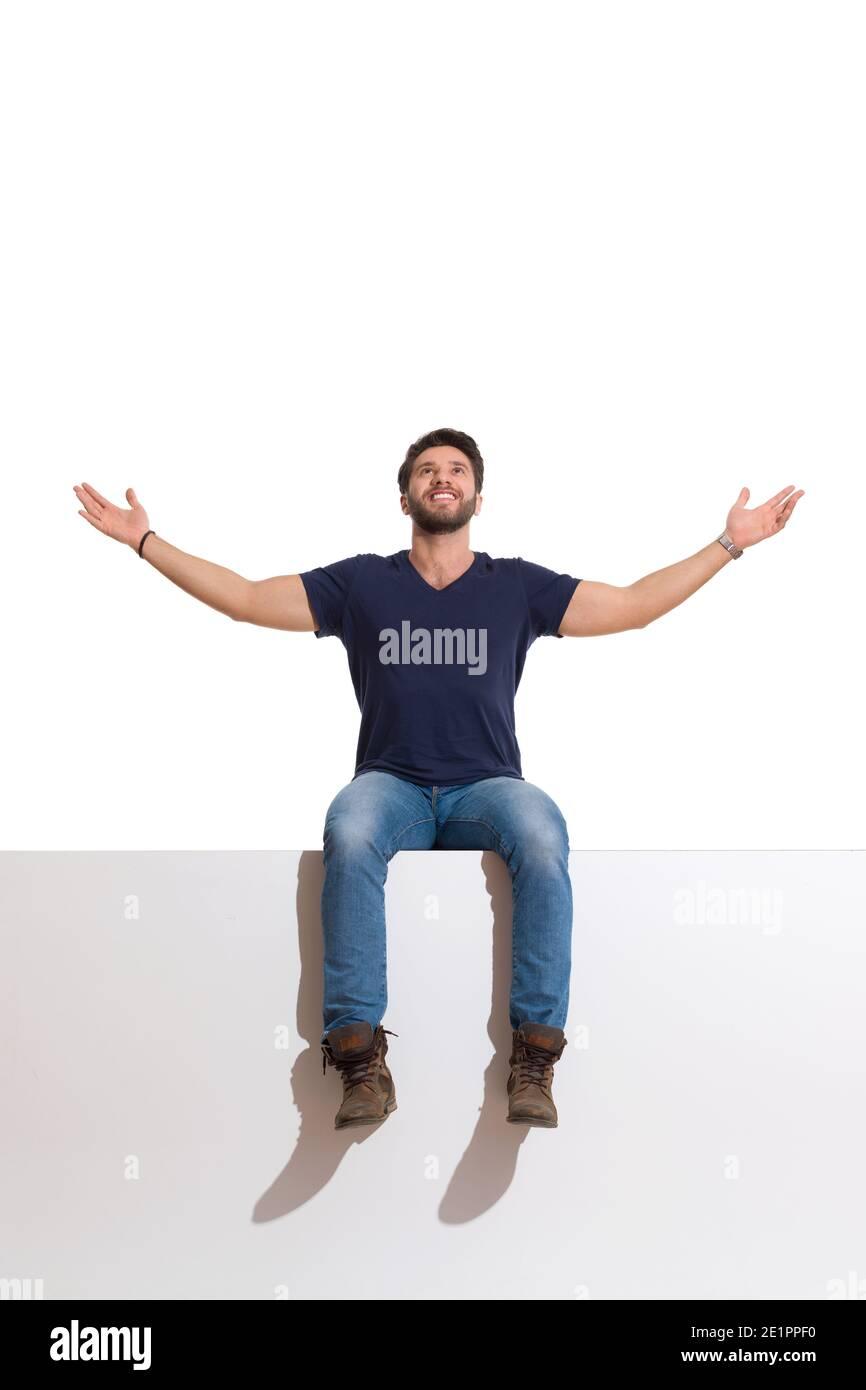 Le jeune homme heureux en bottes, jeans et chemise bleue est assis sur un haut avec les bras étirés, regardant vers le haut et souriant. Prise de vue en studio sur toute la longueur isolée sur Banque D'Images