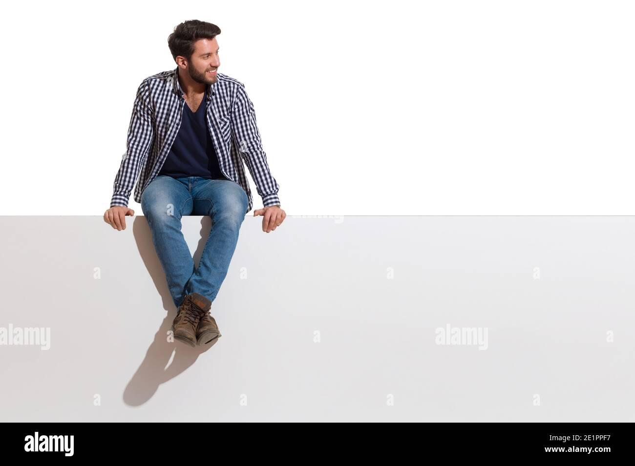 Beau jeune homme décontracté est assis sur un haut de bannière blanche avec les jambes croisées, souriant et regardant le côté. Prise de vue en studio sur toute la longueur isolée sur Banque D'Images