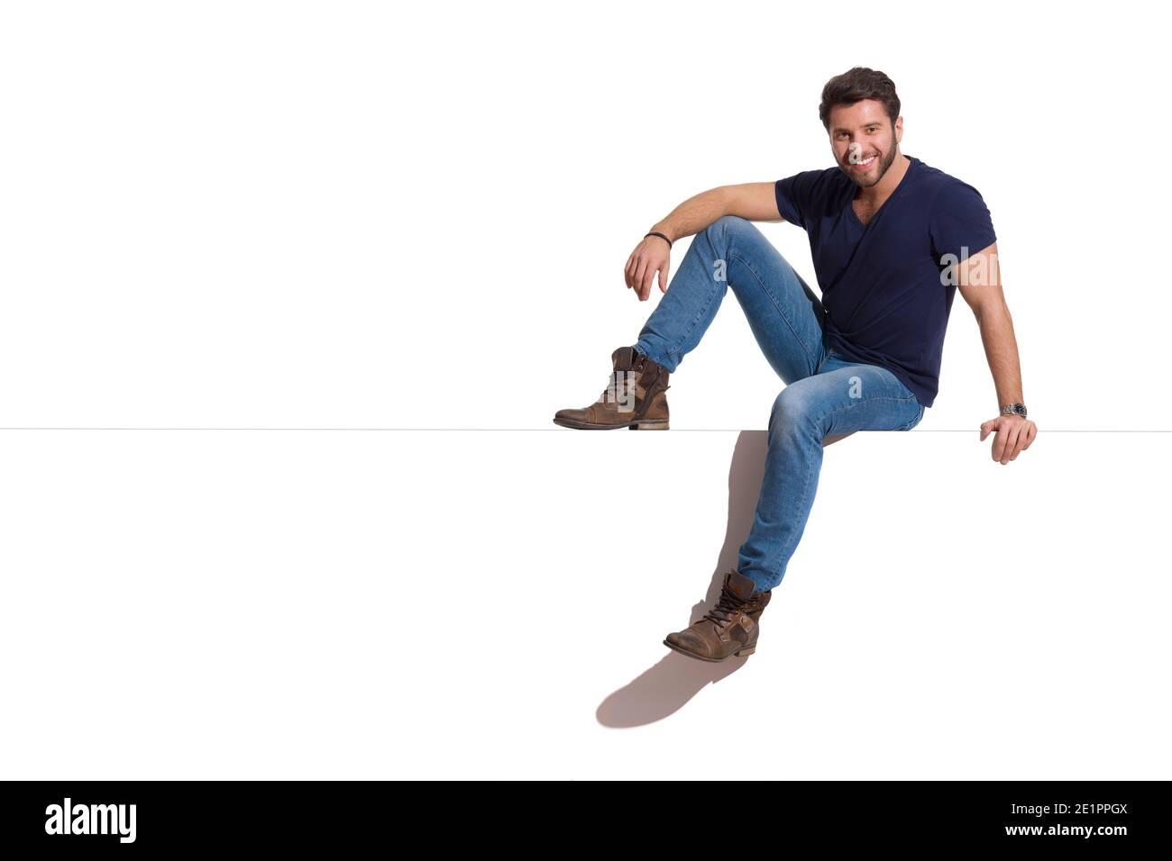 Jeune homme décontracté est assis détendu sur un sommet, regardant l'appareil photo et souriant. Prise de vue en studio sur toute la longueur isolée sur blanc. Banque D'Images