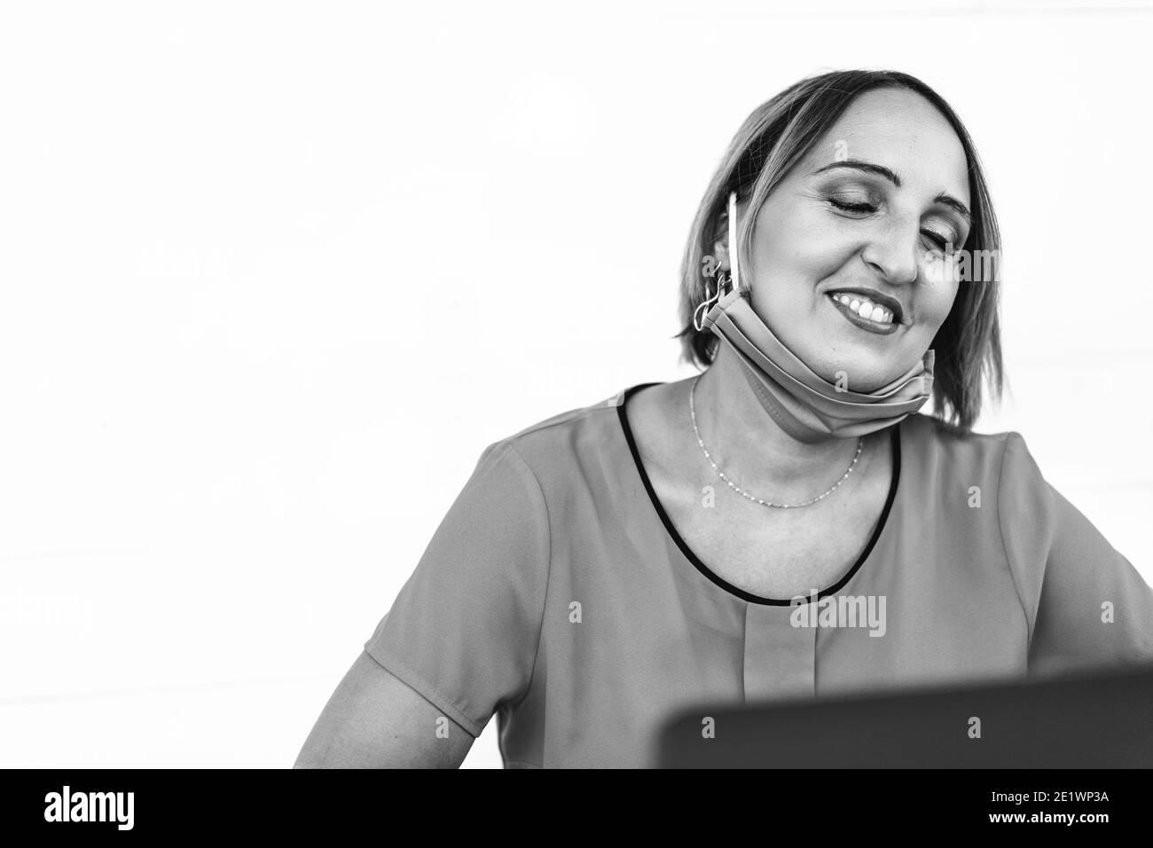 Femme souriante de 40 ans portant un masque de protection ouvert Utilisation d'un ordinateur portable à la fin de l'épidémie de coronavirus - Femme entrepreneur ou influenceur h Banque D'Images
