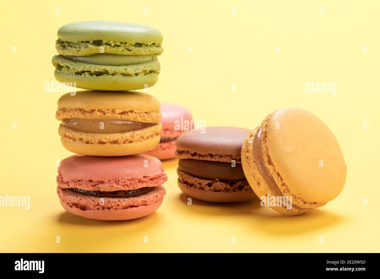 Pâte de macarons français pastel aux saveurs de framboise, citron, chocolat et pistaches sur fond jaune clair Banque D'Images