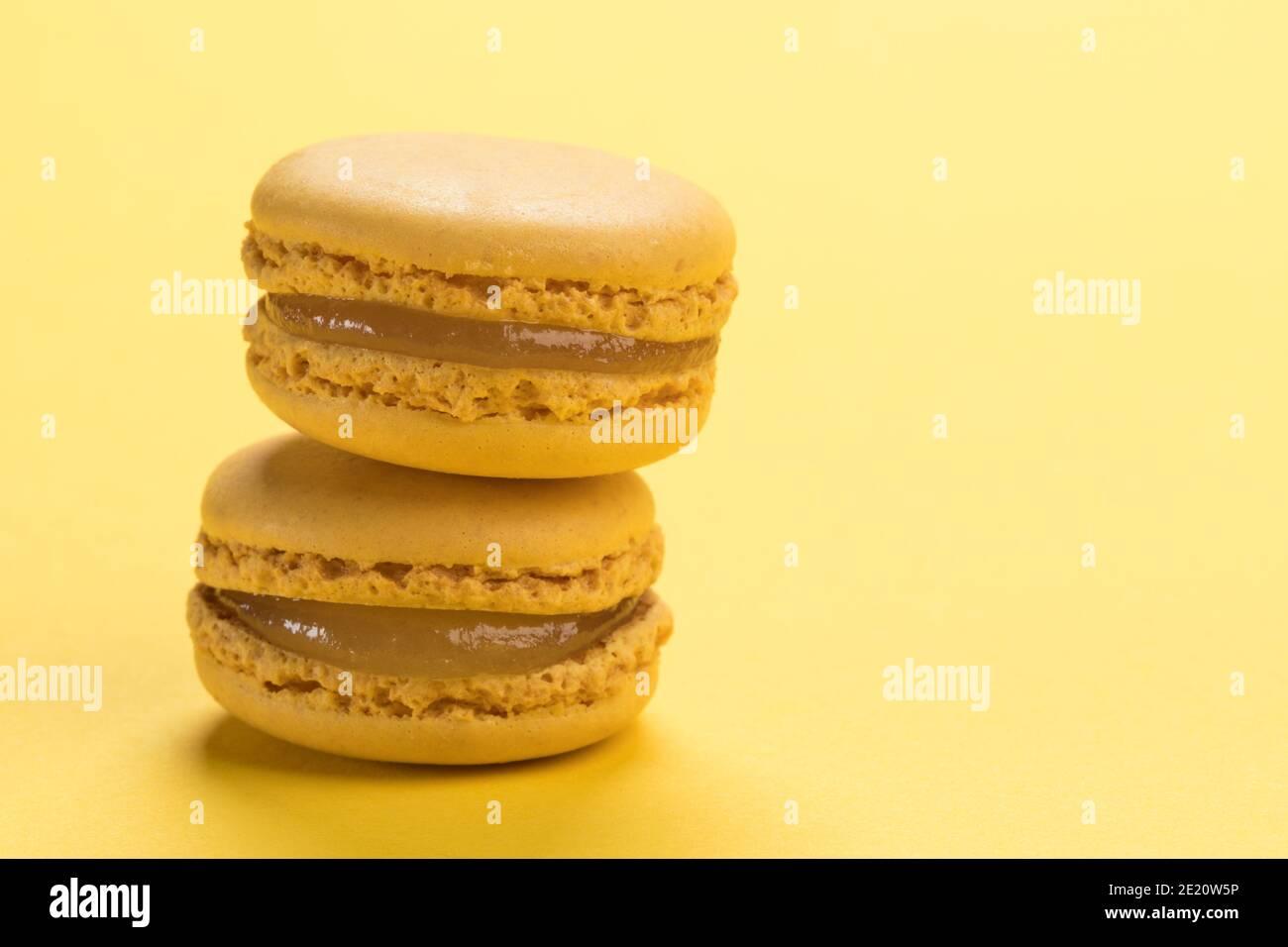 Gros plan de pâte de macarons français au citron sur pastel arrière-plan jaune avec espace de copie Banque D'Images