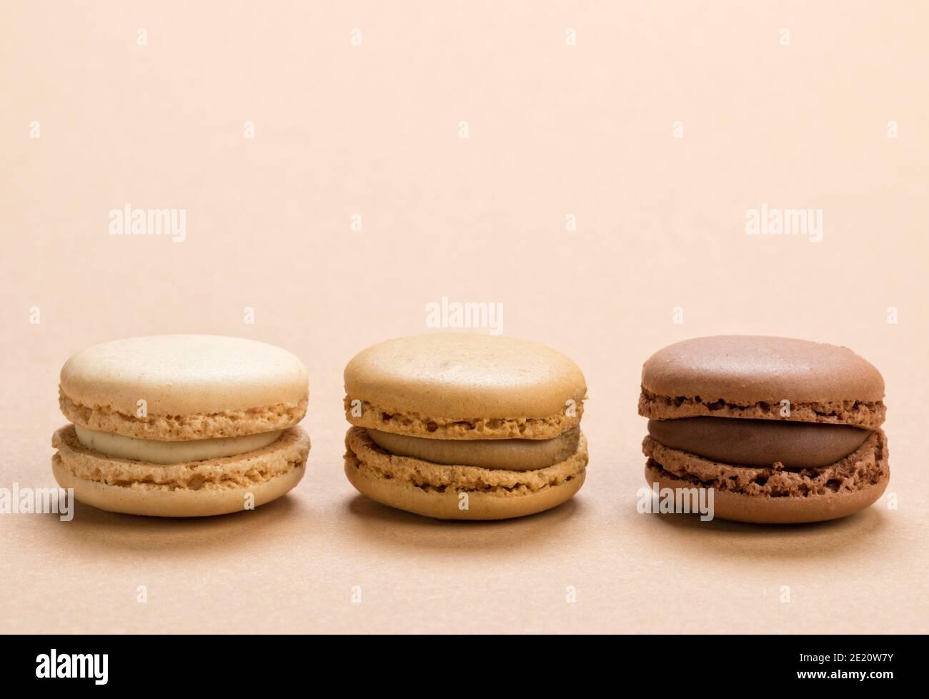 Gros plan de pâte de macarons fourrée de vanille, de café et de sauce au chocolat sur fond brun clair Banque D'Images