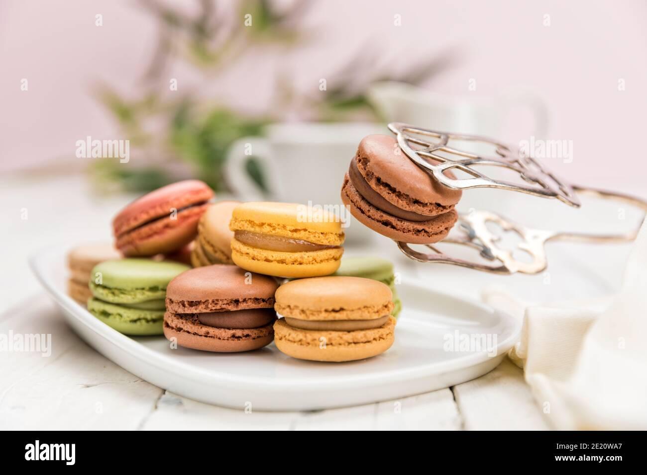 Assortiment de pâtisseries françaises de macarons sur table de café, se concentrer sur un chocolat aromatisé à l'aide de pinces à pâtisserie, Banque D'Images