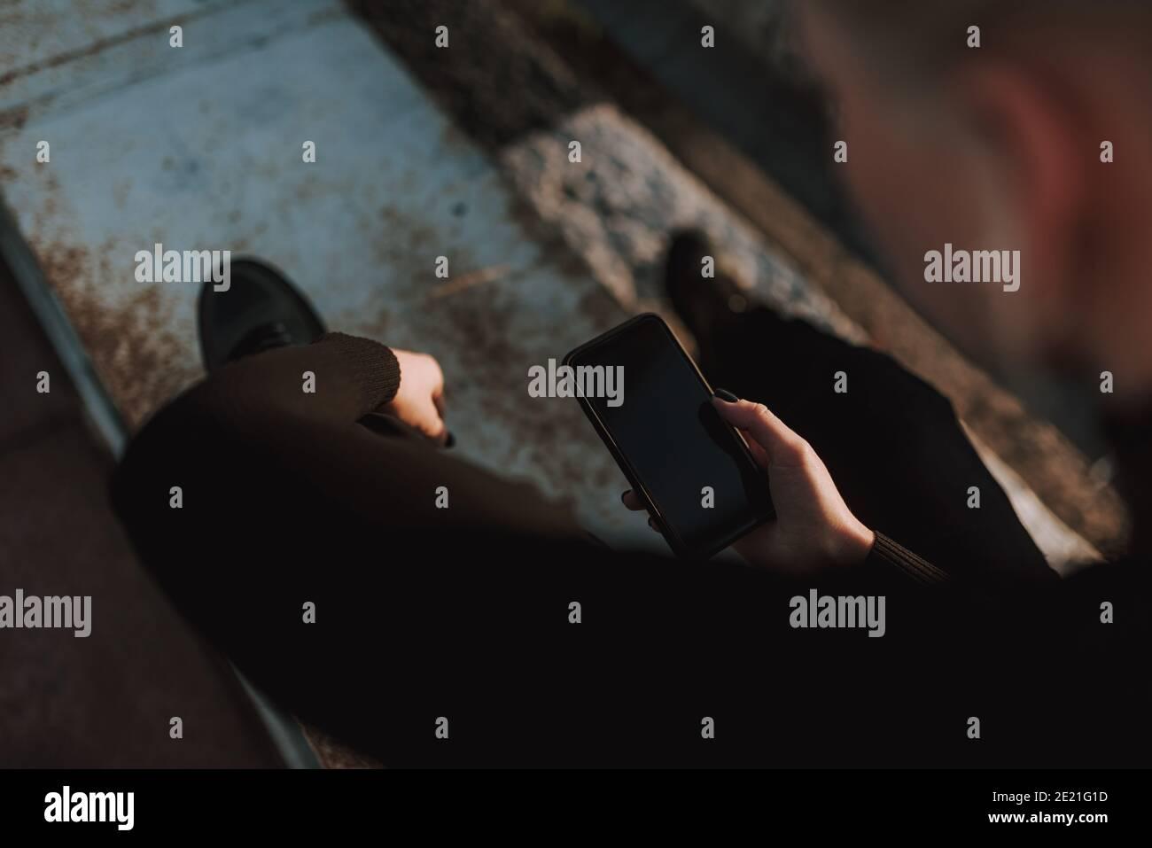 Vue de dessus des mains de dame en utilisant un smartphone tout en étant assis en métal construction à l'extérieur Banque D'Images