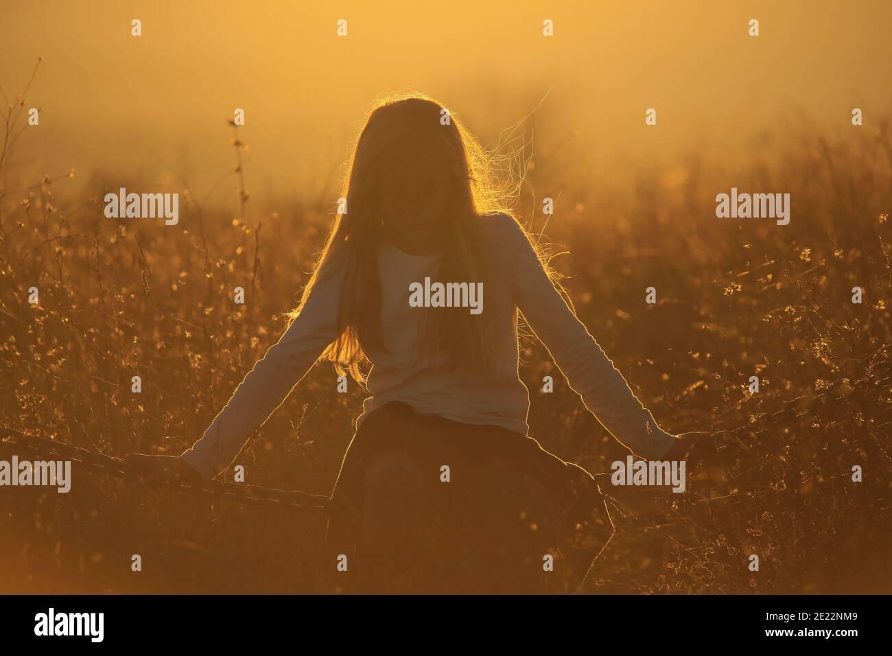 La jeune fille Blonde est assise sur une chaîne dans un or coucher de soleil Banque D'Images