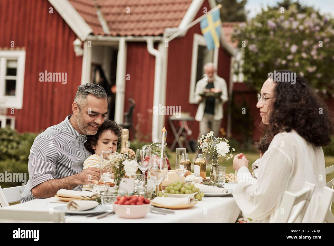 Family having meal in garden Banque D'Images