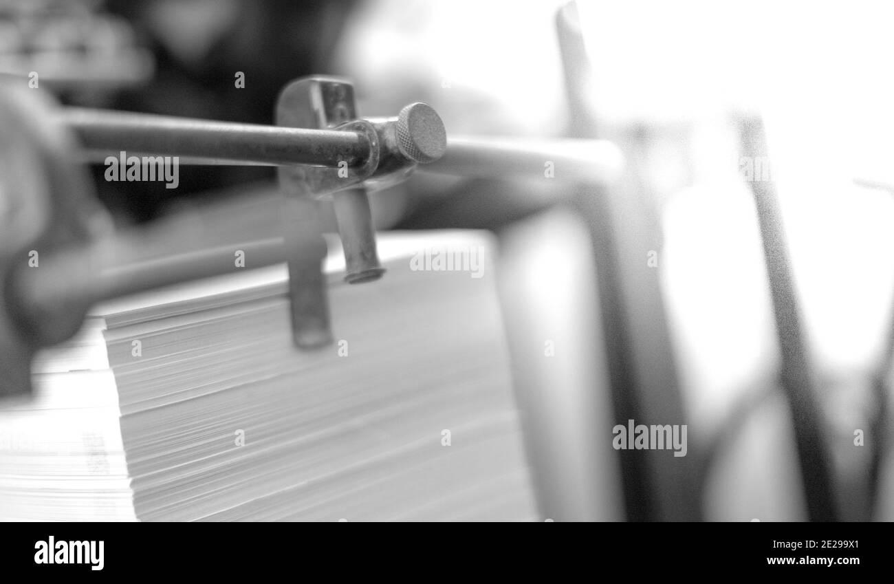 Les feuilles de papier imprimées sont servies dans l'ancienne machine de typographie d'impression avec le concept rouillé. Petite industrie d'impression. Le concept d'échelle de gris Banque D'Images