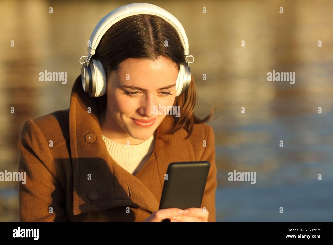 Femme satisfaite écoutant de la musique avec un casque et un téléphone portable sur la plage au coucher du soleil en hiver Banque D'Images