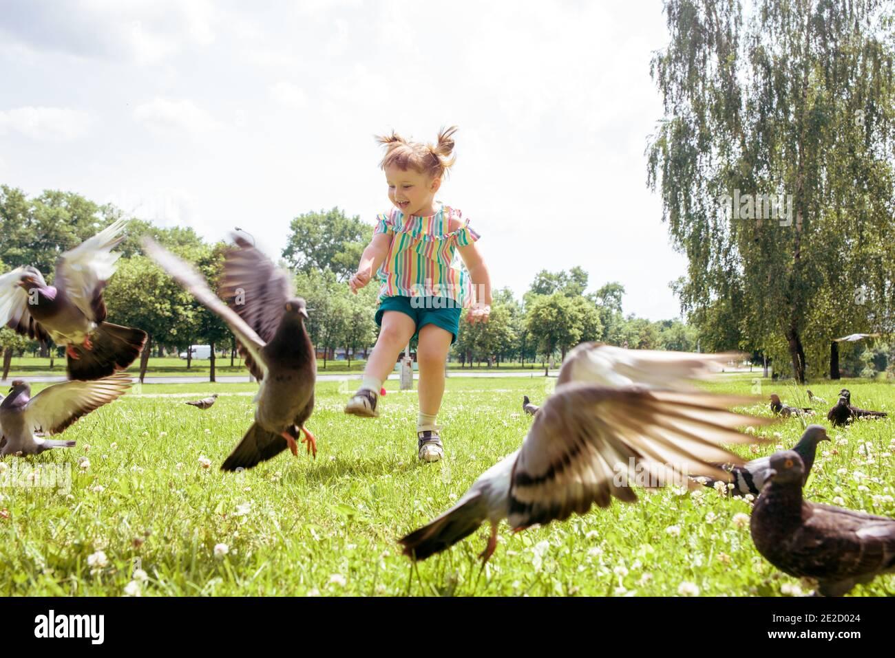 Petite fille scares pigeons jeu amusant été. Écologie, court sur l'herbe dans le parc de la ville à l'extérieur, style de vie Banque D'Images
