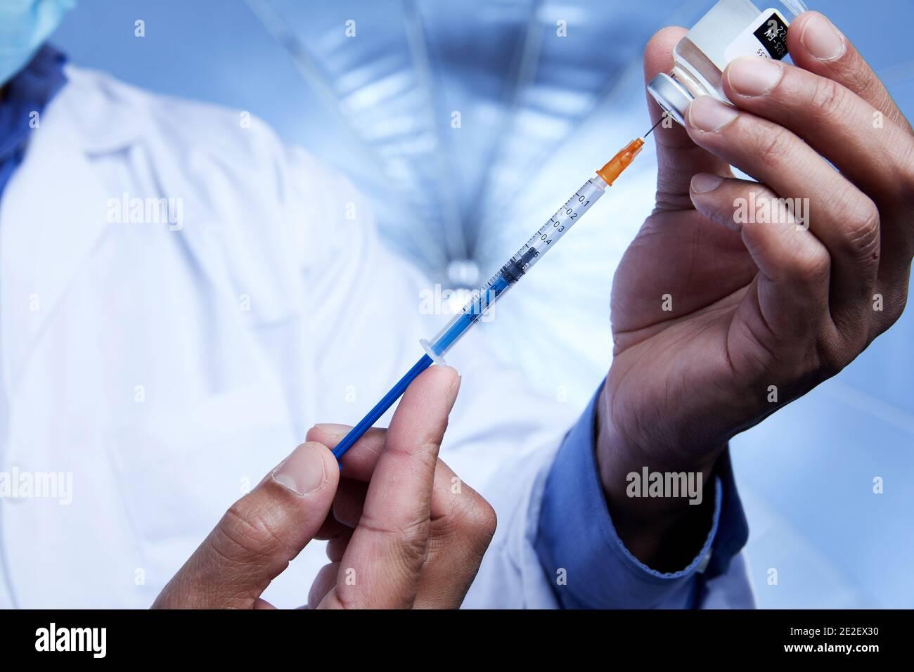 Gros plan d'un scientifique afro-américain interagissant avec une seringue et un flacon en verre de vaccin liquide en laboratoire. Banque D'Images