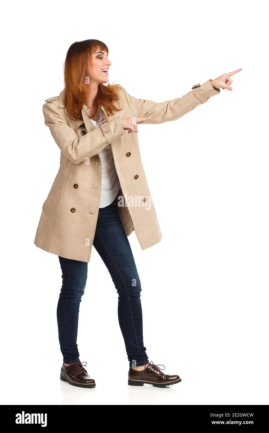 Jeune femme en pelage beige non boutonné, jeans et chaussures brunes est debout, pointant, regardant loin et riant. Prise de vue en studio sur toute la longueur isolée sur le coup Banque D'Images
