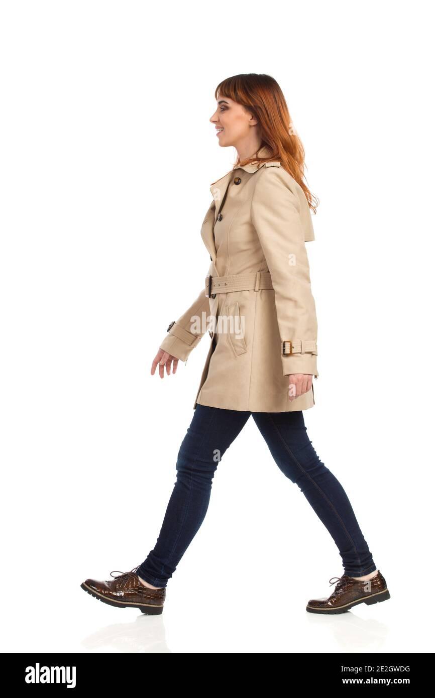 Une jeune femme confiante marche avec un manteau beige, un Jean et des chaussures marron. Vue latérale. Prise de vue en studio sur toute la longueur isolée sur blanc. Banque D'Images