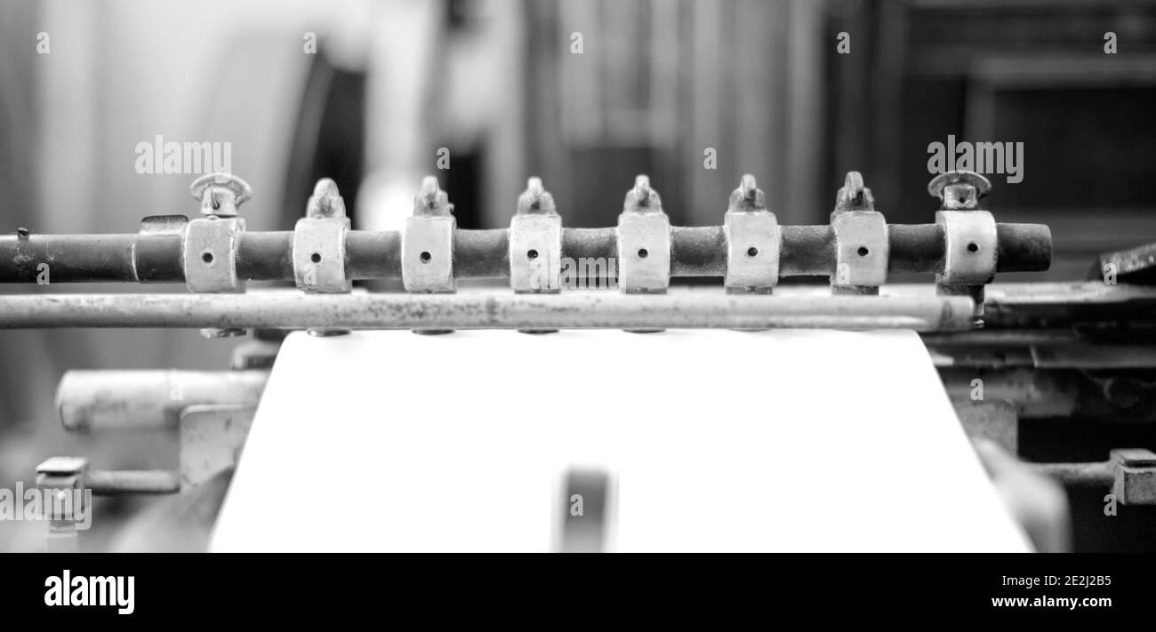 L'effet photo avec la presse d'impression prend la feuille de papier en action dans la ligne de production d'impression, l'ancienne machine avec le rouillé pour le TH Banque D'Images