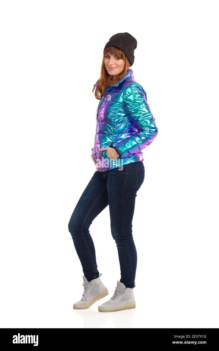 Belle jeune femme en duvet, casquette d'hiver, jeans et baskets, les mains dans la poche et souriant. Long studi Banque D'Images