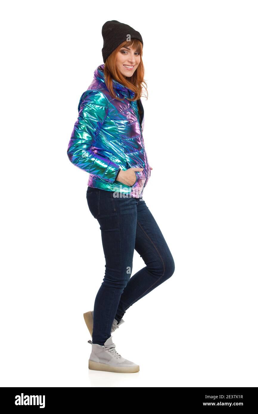Jeune femme en duvet, jeans, baskets et casquette brillants et vibrants, debout, tenant la main dans la poche et souriant. Vue latérale. Studios pleine longueur s Banque D'Images