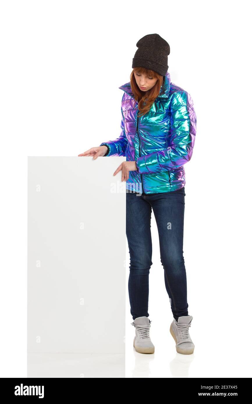 Jeune femme en duvet, casquette d'hiver, jeans et baskets est debout, avec un écriteau blanc, regardant vers le bas et lisant. Longueur totale Banque D'Images