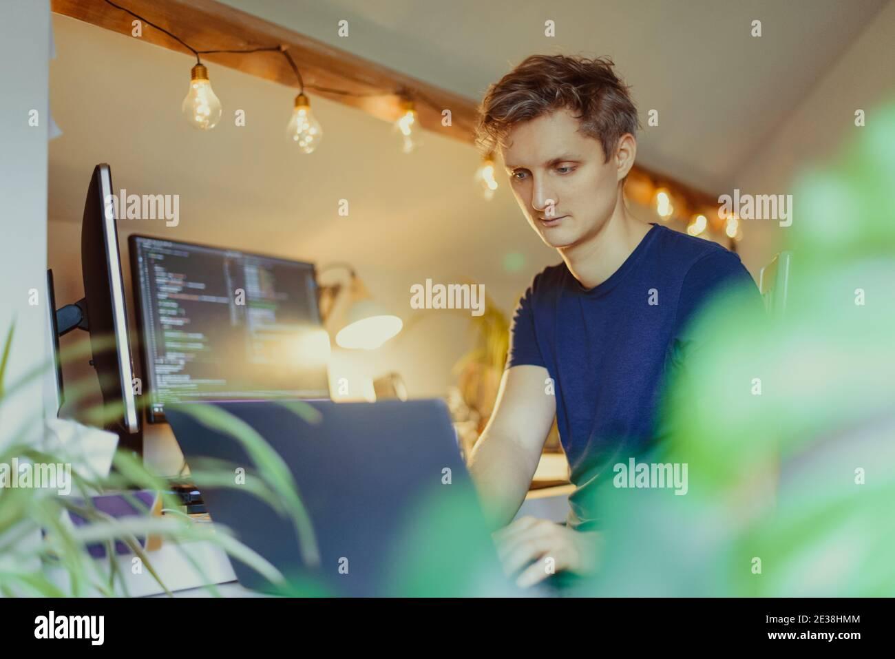 Un homme assis à un bureau travaillant à la maison sur son ordinateur. Un programmeur informatique spécialisé écrit du code sur son pc et son ordinateur portable. Bureau à distance du développeur Banque D'Images