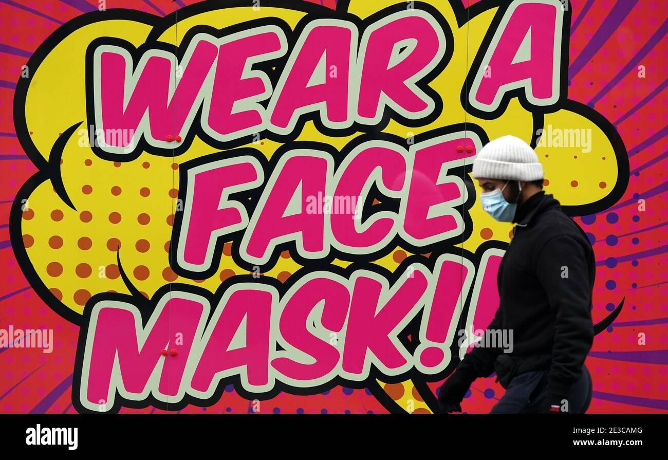 Une personne passe devant un panneau indiquant aux gens de porter un masque facial à Nottingham pendant le troisième confinement national de l'Angleterre pour freiner la propagation du coronavirus. Date de la photo: Lundi 18 janvier 2021. Banque D'Images