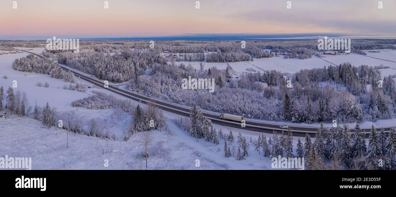 Spectaculaire photo aérienne d'hiver de la route européenne E4 près de la ville d'Umea. Pittoresque forêt de pins scandinaves surgelé, couverte de neige abondante. Banque D'Images