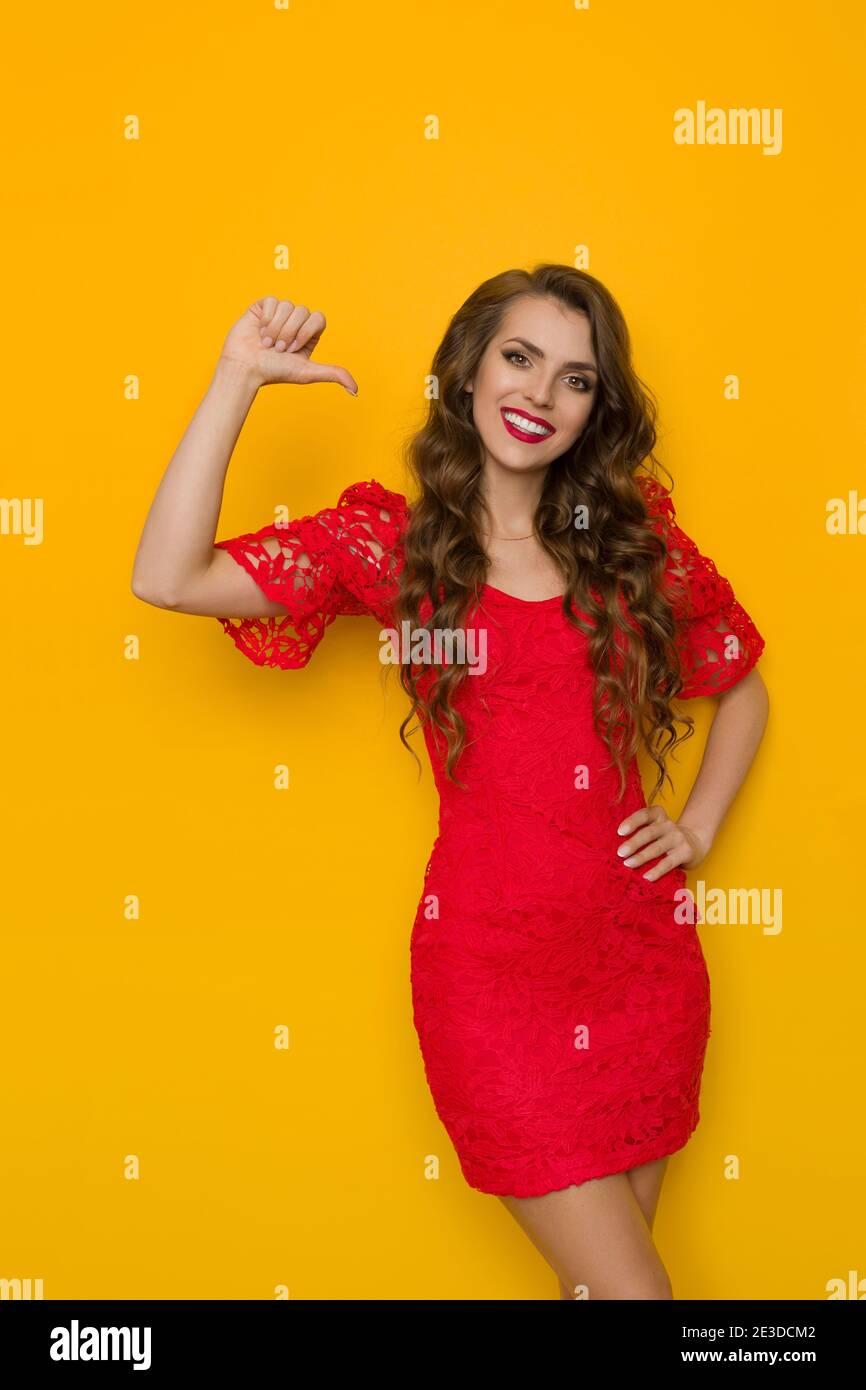 Belle jeune femme en élégante robe en dentelle rouge se pointe vers elle-même et sourire. Trois quarts de long studio tourné sur fond jaune. Banque D'Images