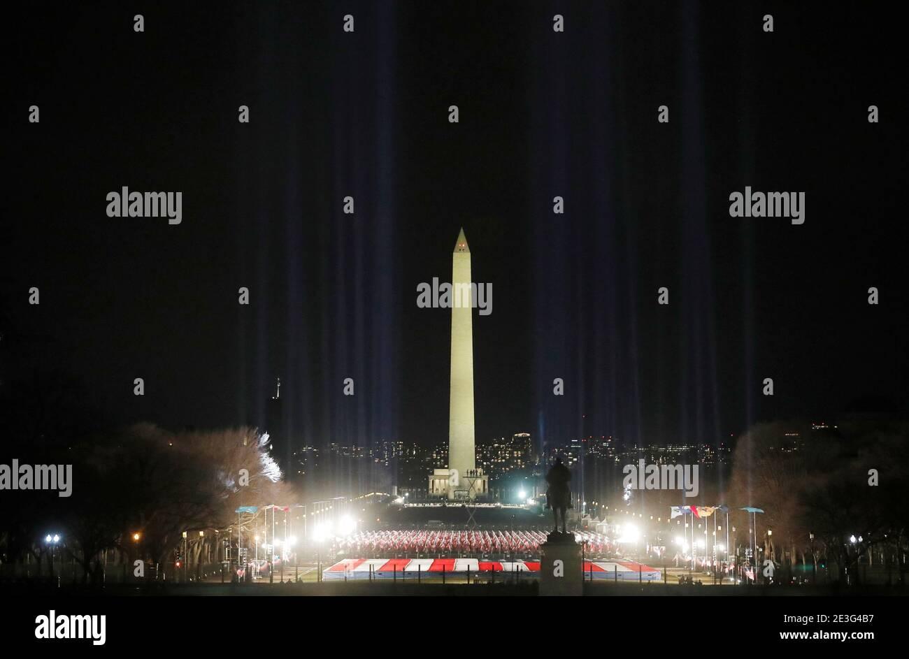 Les projecteurs éclairent le ciel depuis le « champ des drapeaux » du centre commercial national américain en l'honneur de l'inauguration prochaine du président élu des États-Unis, Joe Biden, à Washington, aux États-Unis, le 18 janvier 2021. REUTERS/Jim Bourg Banque D'Images