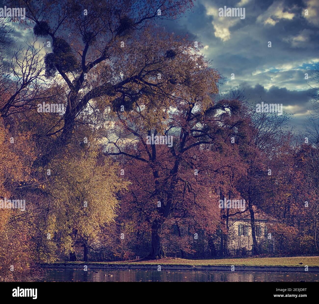 Vue d'automne d'une villa ancienne romantique entourée d'un parc vert avec de hauts arbres sur un bord de lac Banque D'Images