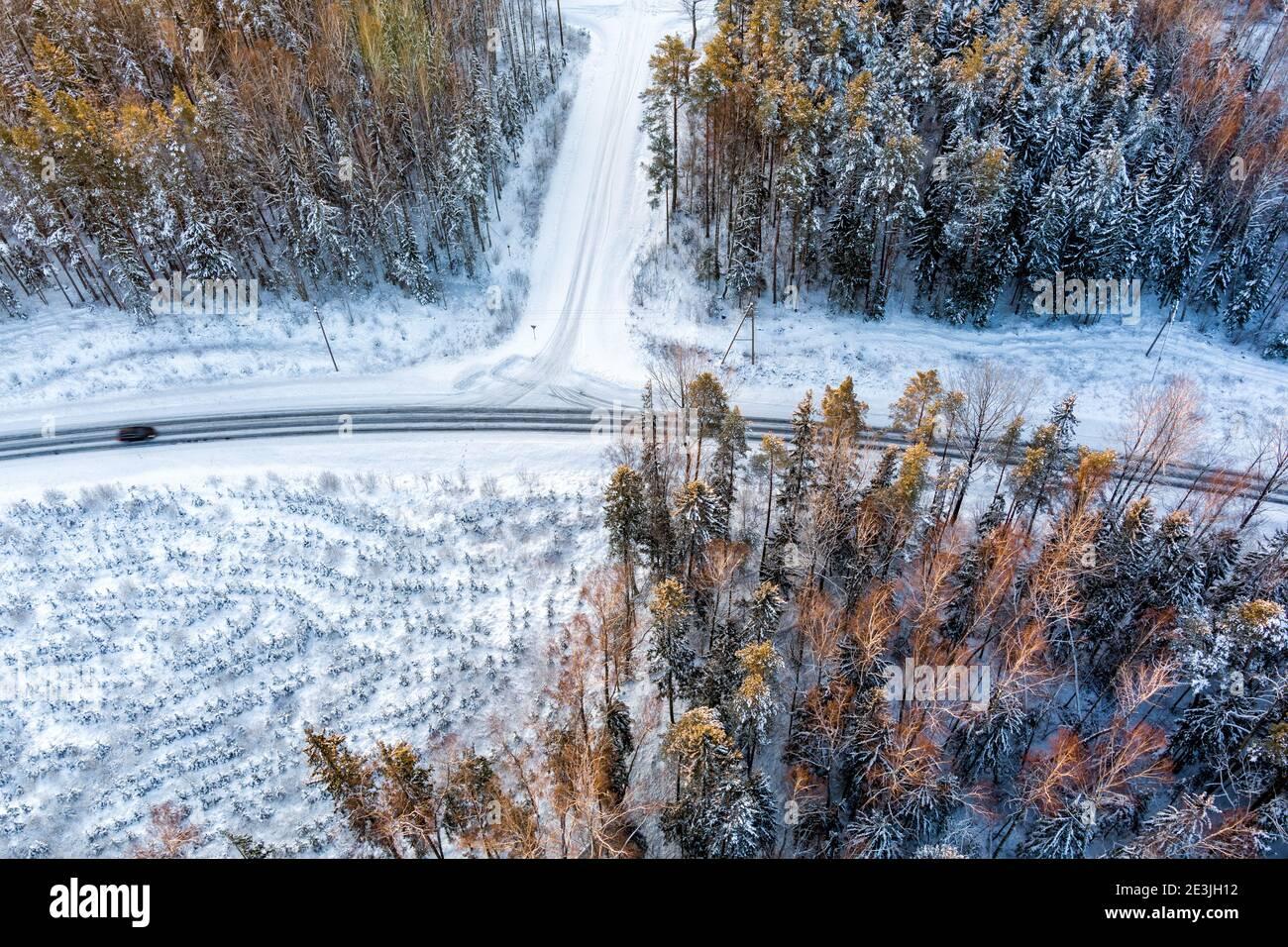 Vue aérienne depuis un drone de voiture sur une neige sinueuse couverte route dans la forêt d'hiver Banque D'Images